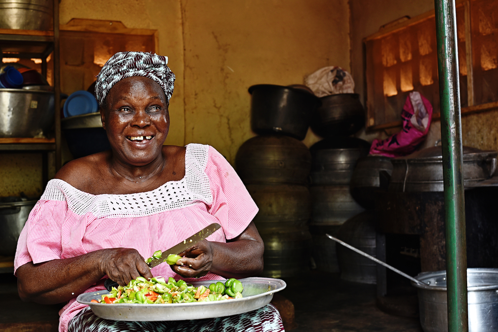 A woman sits in a kitchen cutting vegetables