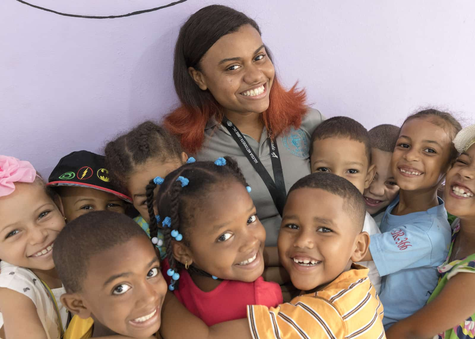 A woman stands with a group of children hugging her