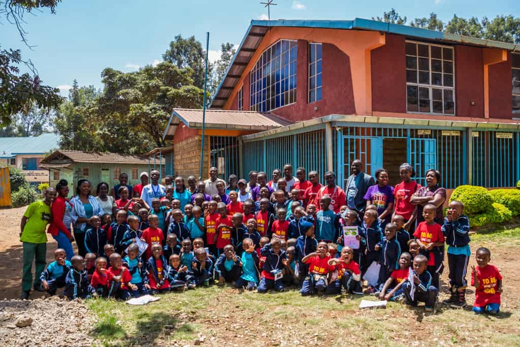 Children and Staff outside a Compassion child development center.