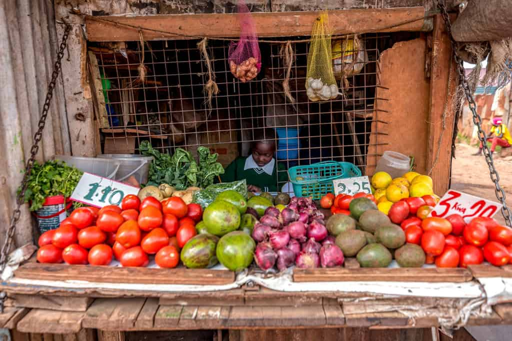 A child sitting behind a display of fruits at her grandmother's shop.