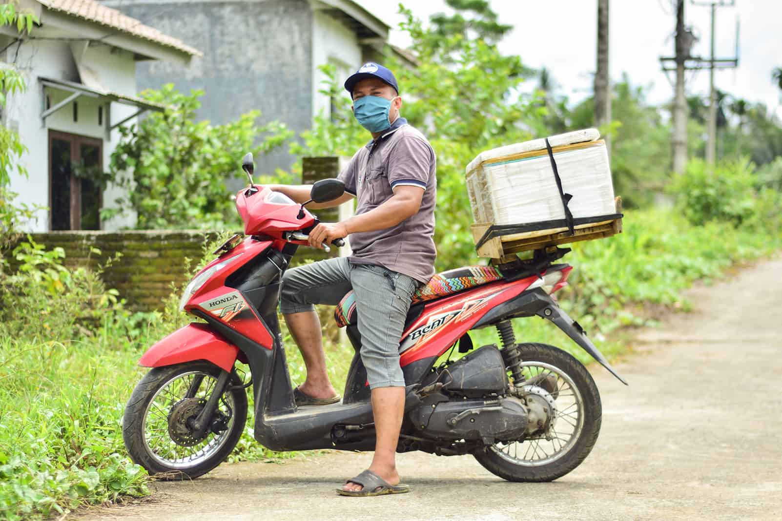 Julius is wearing a gray shirt and green pants, along with a blue face mask. He is sitting on a motorbike that he drives around his community to sell fish. His fish cooler is on the back of his bike.