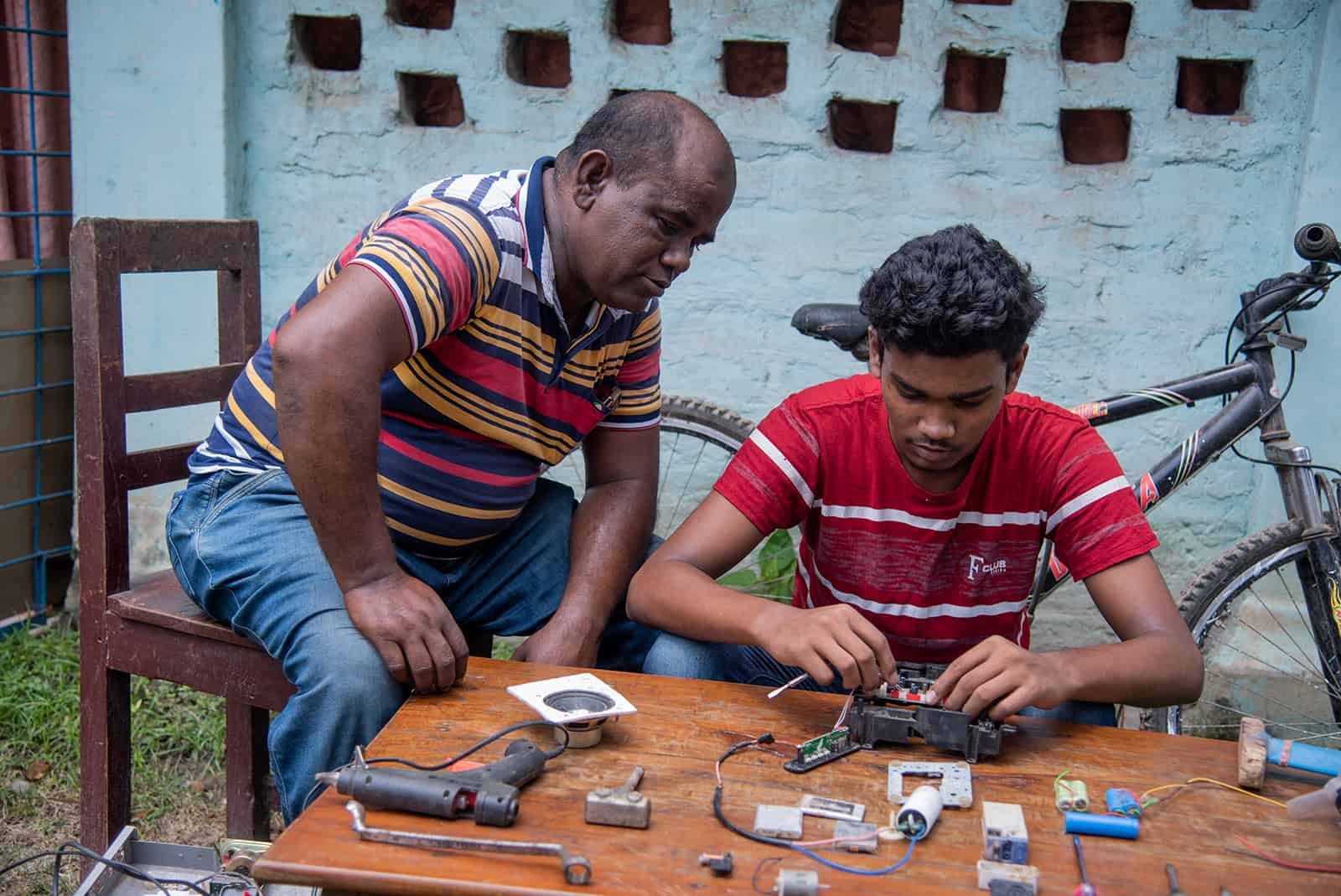 Sanjoy, in a red shirt, and his father, Subhas, in a red, yellow, blue and white shirt, are sitting at a wood table where Sanjoy is working on making a radio from a motherboard. There is a bike in the background.
