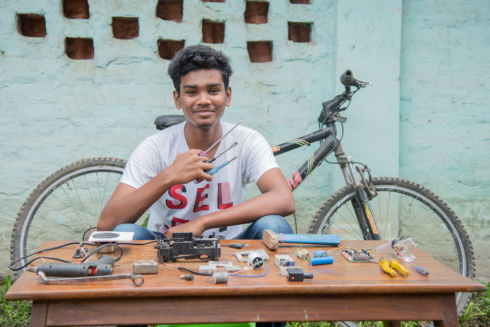 A young man sits at a table covered in tools