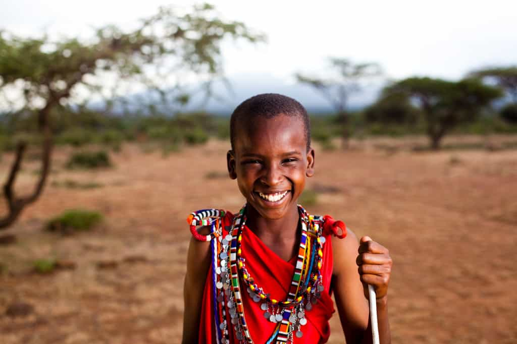 A smiling boy in red stands in front of a plain with trees in the background.