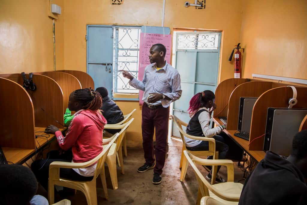 A man teaching computer sill class