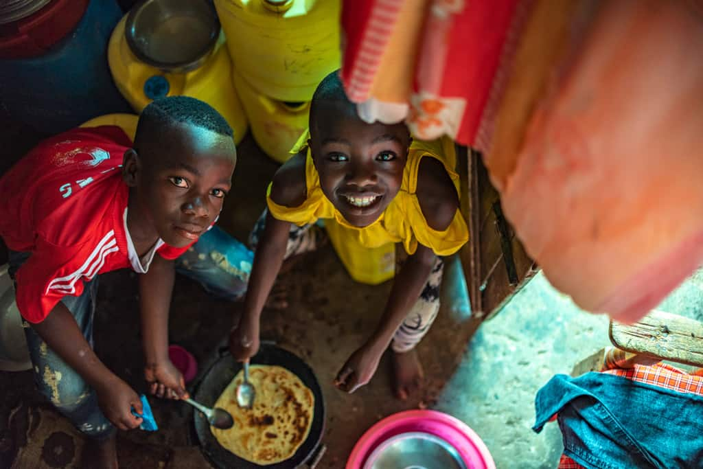 Leach and Moses are seen here helping to make Chapati. They are looking up at the camera and smiling.