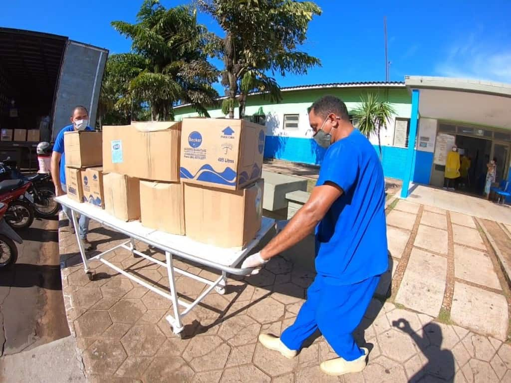 Two men wearing blue scrubs and masks wheeling a cart holding nine boxes of supplies