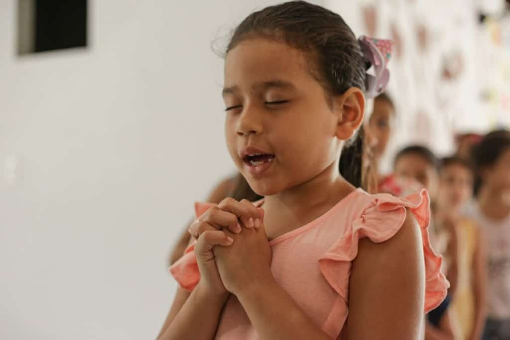 A Brazilian girl wearing pink prays with her eyes closed and hands clasped